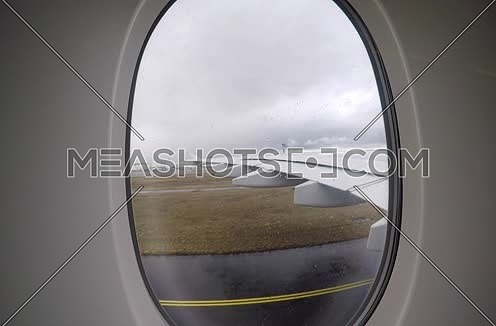 shot from plane window showing wing and runway while the plane is moving in frankfurt airport in Germany