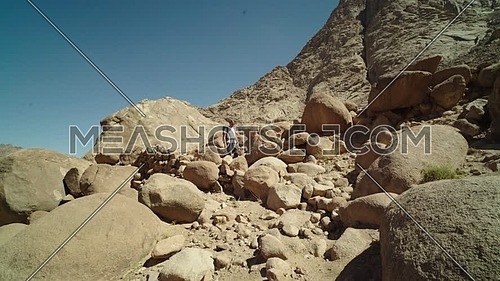 Follow shot for a male tourist wearing a grey travel backpack explore Sinai Mountain for wadi Freij at day.