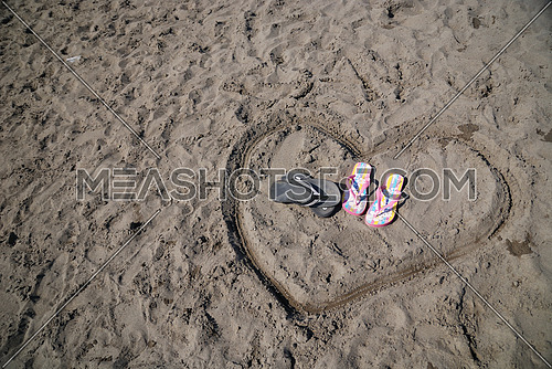 sandals in heart shape draving representing romance on beach concept