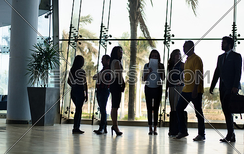 A group of women standing in a meeting while two men cross the hallway