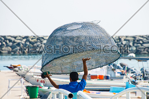 a fisherman holding a fishing net cage