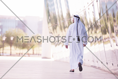 handsome middle eastern business man walking in front of modern office building