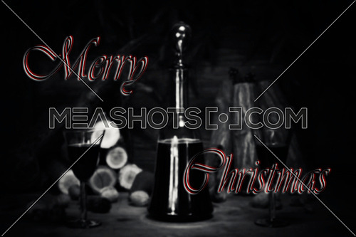 Merry Christmas Sign With Red Wine Vintage Bottle and Glasses Resting On Wooden Table With Stardust and Snowflakes in The Background