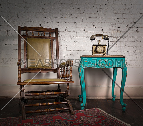 Retro composition of wooden rocking chair, green vintage table and old telephone set over white bricks wall and dark wooden floor with red carpet in a living room