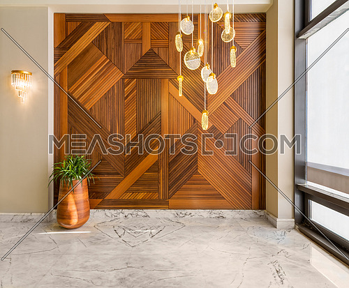 Hall with wood cladding wall decorated with geometrical patterns, tall rounded wooden planter with green bushes, contemporary glass tall chandelier, big window, and white marble floor in modern house
