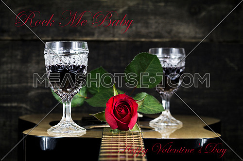 Red Rose and Wine Glasses Resting On Acoustic Guitar With Sign Rock Me Baby. Valentine's day concept
