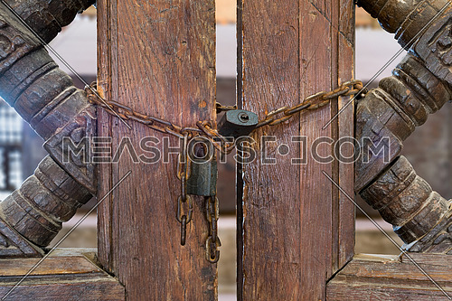 Old rusted padlocks and rusted chain on a half closed wooden interleaved double door