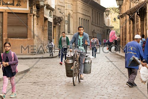 Milk seller on a bicycle in El Moez street in Cairo early morning