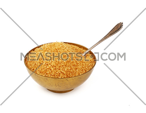 Close up one vintage bronze metal bowl full of raw brown cane sugar with antique spoon, isolated on white background, high angle view