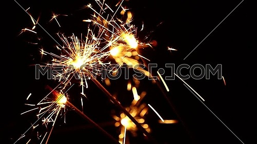 Close up group of several firework sparklers over black background, low angle side view, selective focus