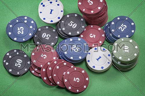 Different types of poker chips on green background