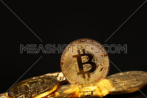 Close up heap of golden bitcoin physical coins over black background with copy space, low angle view, selective focus