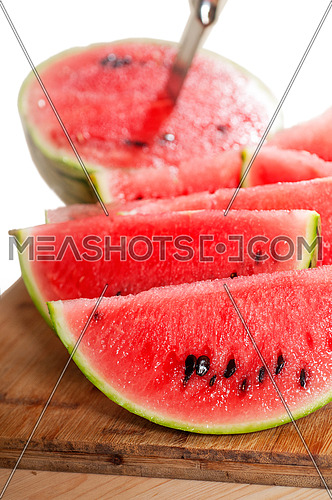 fresh ripe watermelon sliced on a  wood table with knife