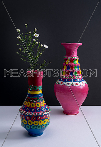 Still life of two artistic painted colorful handcrafted pottery vases, little green branches, and small white flowers with harsh shadow on white table and black wall