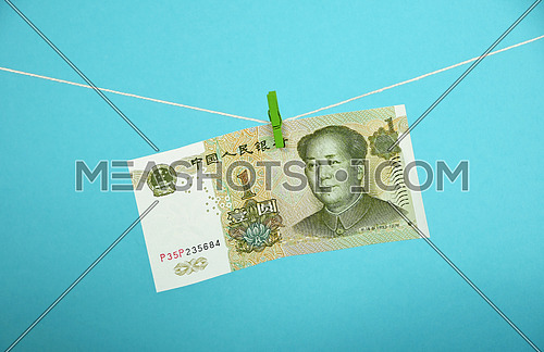 China economy growth, strengthening of Chinese yuan illustrated, one yuan banknote hanged ascending with pin at rope over blue background