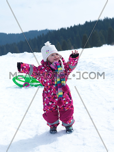 little baby girl have fun on fresh snow and slide on sleddges at beautiful sunny winter day