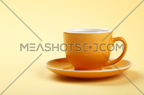 Close up one full yellow cup of tea or coffee on saucer over pastel paper background, low angle side view