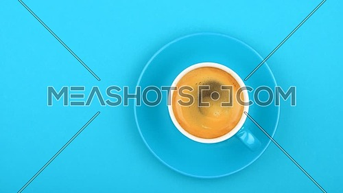 Close up one full white cup of espresso coffee and saucer over pastel blue paper background with slow motion animated spin of coffee froth