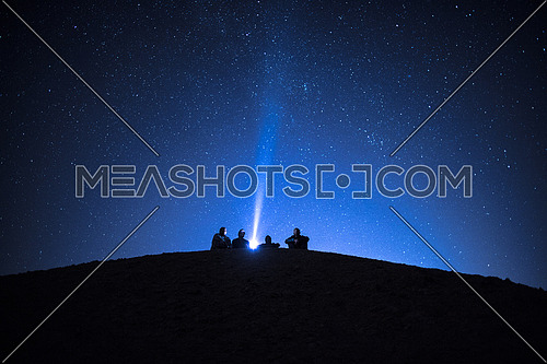 Group of friends stargazing in the desert at Night