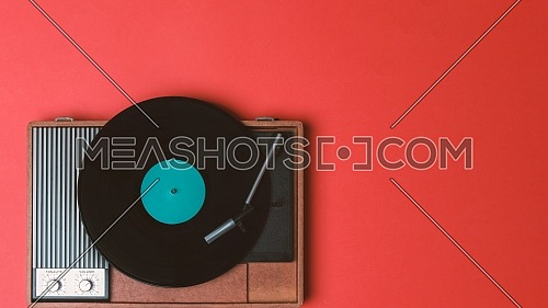 Vintage vinyl player and turnable on a red background. Entertainment 70s. Listen to music. Top view.