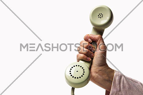 Hand holding a light green retro phone isolated on white background