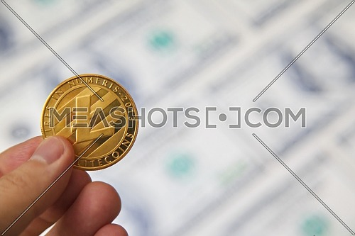 Close up shot for Litecoin in male hand, dollar background.