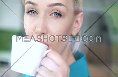 Blond looking thorugh window and drinking coffee