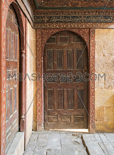 Two wooden aged ornate vaulted perpendicular doors on stone bricks walls, Medieval Cairo, Egypt