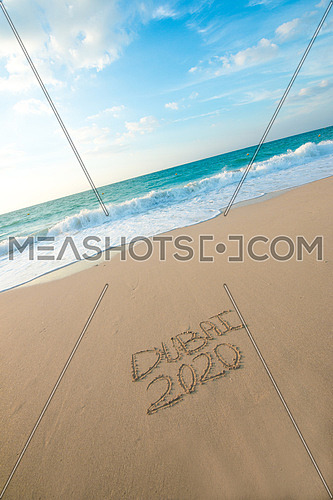 in the picture at the beach  written on the sand Dubai 2020