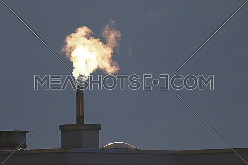 Heating oil going into the air from a filtered stack on a roof