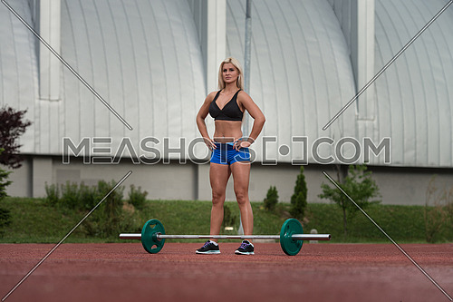 Portrait Of A Young Woman Preparing For Dead Lift Exercise Outdoor