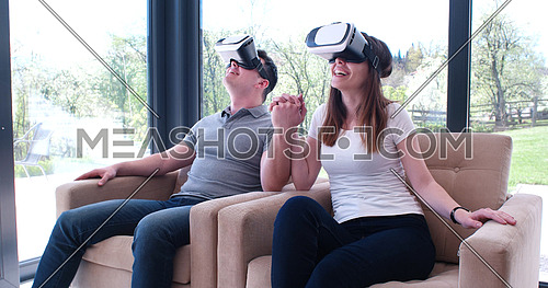 Couple using virtual reality headset in living room at home  people playing game with new trends technology