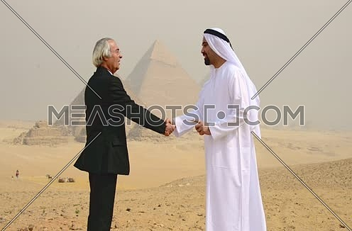 successful emiratie and egyptian business men at pyramids shaking hands