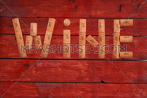 Word WINE shaped by natural wooden wine bottle corks of different vintage years over background of red vintage rustic aged painted wooden planks