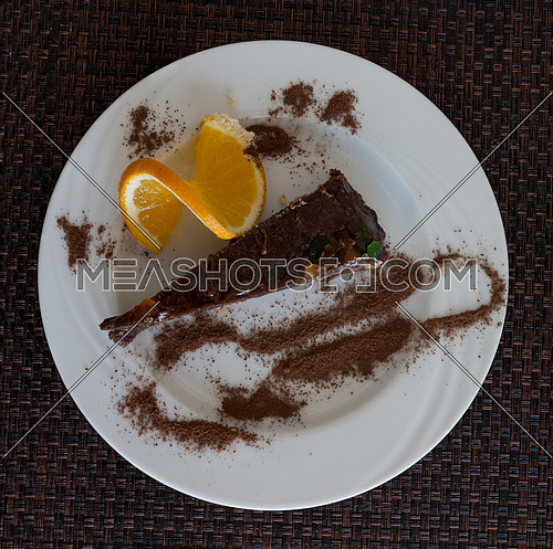 In the picture a slice of chocolate cake garnished with candied fruit, served on a white plate with a slice of orange and cocoa,view on above.