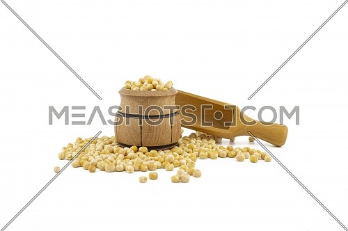 Dried peas spilling from a wooden barrel and wooden scoop isolated on a white background
