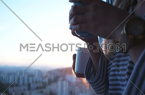couple drinking coffee with sun flare coming from window. Sunset and couple