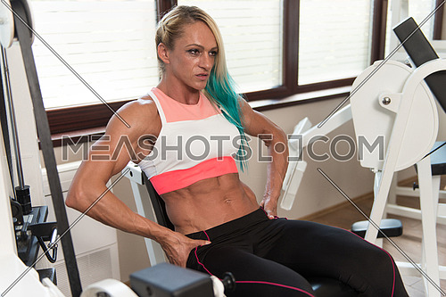 Middle Aged Woman Doing Leg Exercises With Machine In Gym