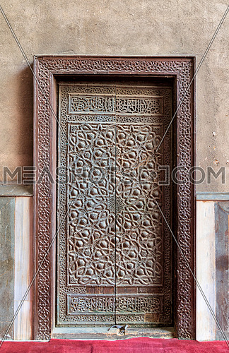 Closed wooden aged door with ornate bronzed geometric patterns at Sultan Hassan Mosque, Cairo, Egypt