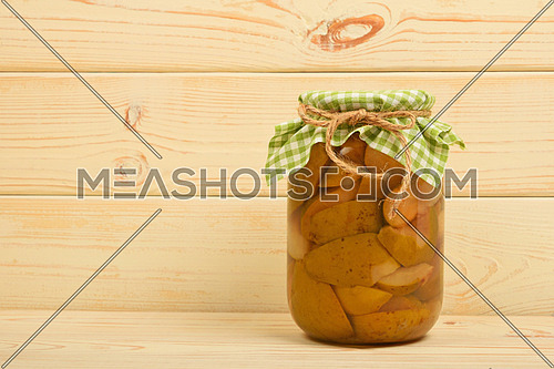 One glass jar of homemade pear compote with green checkered textile top decoration at beige painted vintage wooden surface