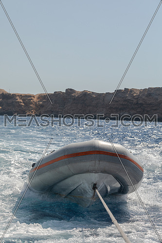 Close shot for Inflatable boat (Zodiac) hanged to backside boat at day.