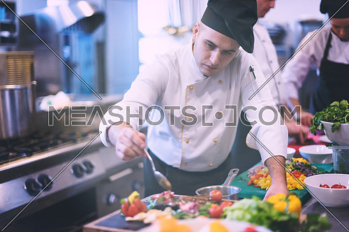Chef finishing steak meat plate with Finally dish dressing and almost ready to serve at the table