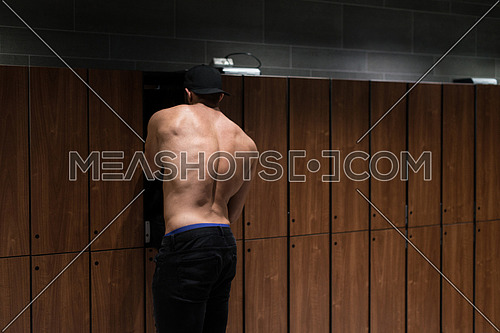 Young Fit Adult Man Changing Clothings In Locker Room Of Gym Facility