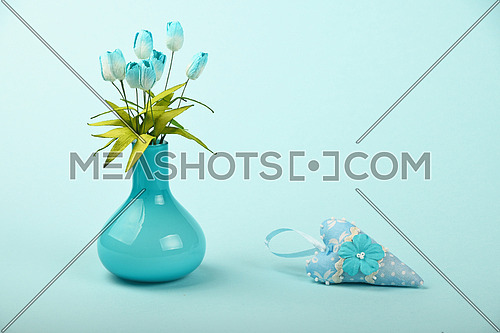 One small textile toy heart and mulberry silk tulip flowers bouquet in glass vase on tender blue design paper background
