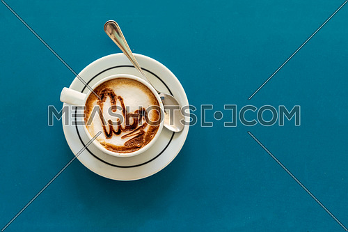 Capuccino on a cup with foam and above the foam the inscription Cuba on a turquoise background