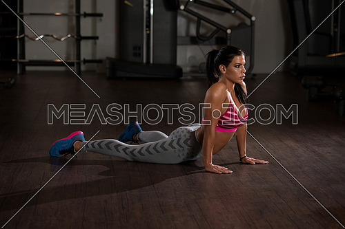 Young Woman Doing Stretching Exercises On The Floor At The Gym