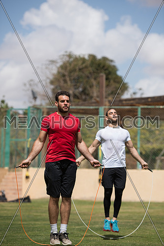 Young middle eastern athletic guys exercise skipping rope outdoors