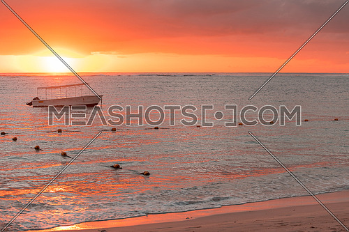 Fishing boat anchored near the shore of the beach at orange sunset,mauritius beach Flic and Flac.
