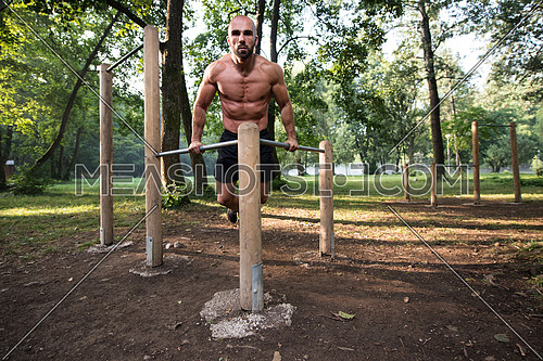 Young Athlete Working Out Triceps In An Outdoor Gym - Doing Street Workout Exercises