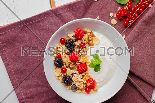 Oat and raspberry yogurt bowl in a purple table cloth